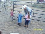 The little cowpokes put money in the hat for the cowboy offering